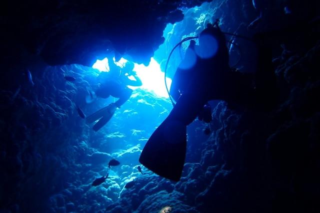 岩のトンネルを潜るダイバー