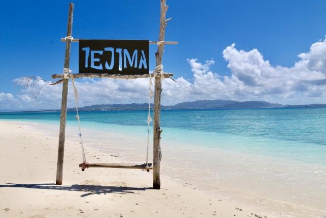 浜辺にあるiejimaと書かれた旗とブランコ